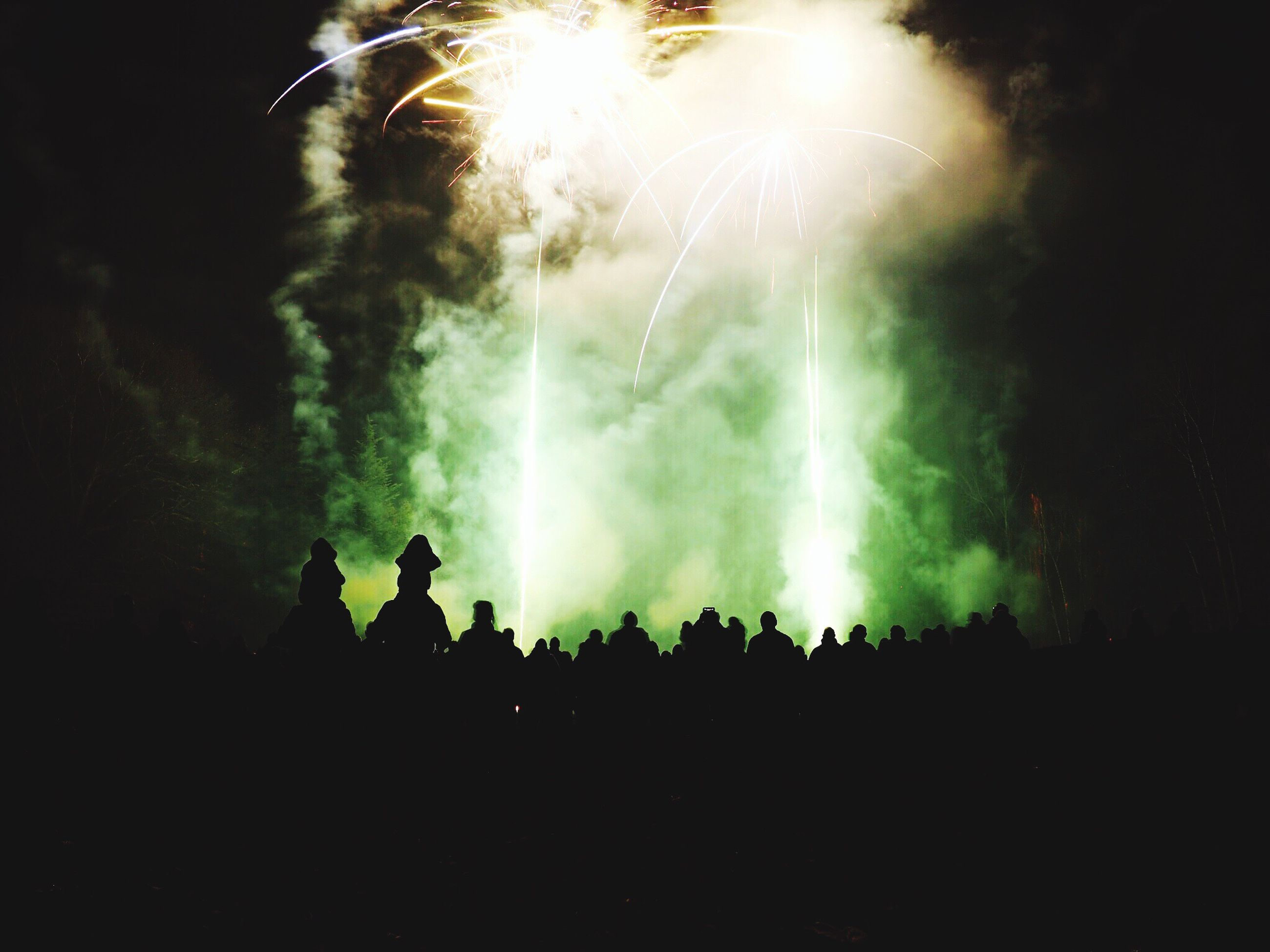 night, arts culture and entertainment, men, event, silhouette, illuminated, lifestyles, fire - natural phenomenon, leisure activity, smoke - physical structure, glowing, sparks, burning, firework display, enjoyment, celebration, large group of people, light - natural phenomenon, motion