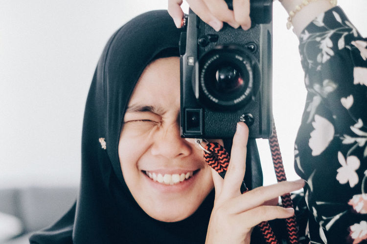 Camera Girl Portrait One Person Real People Smiling Headshot Holding Leisure Activity Technology Indoors  Lifestyles Young Adult Front View Teeth Happiness Young Women Photography Themes Toothy Smile Emotion Women Digital Camera Woman In Hijab