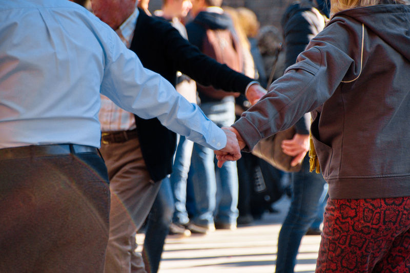 Rear view of friends standing on street holding hands while traditional dance, mallorca