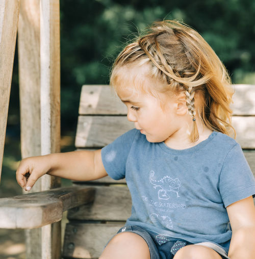 Cute girl looking away while sitting on wood