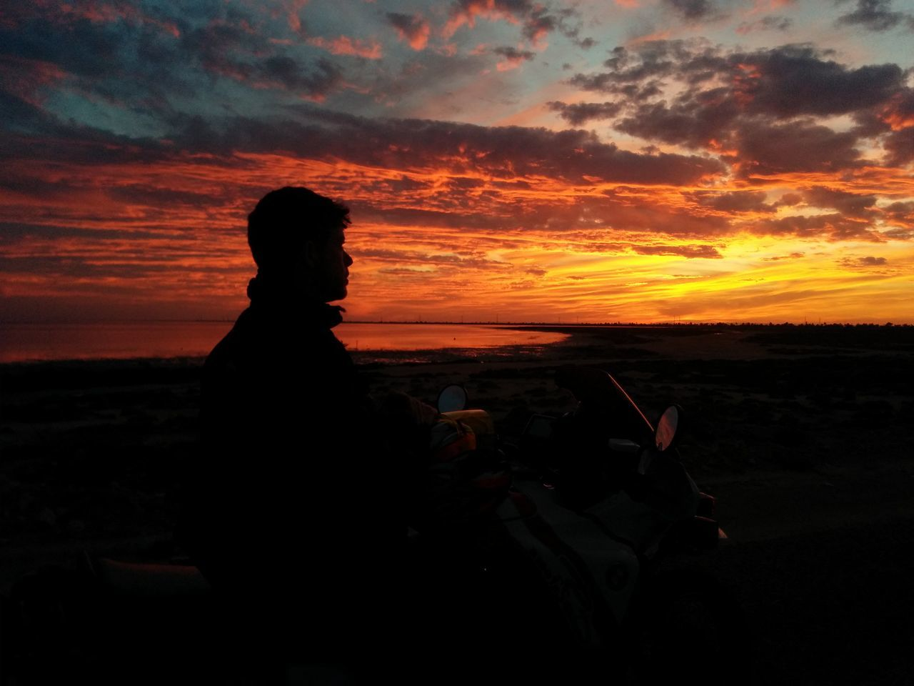 sunset, sky, nature, beauty in nature, scenics, silhouette, cloud - sky, real people, leisure activity, tranquility, one person, sitting, lifestyles, beach, outdoors, vacations, women, people