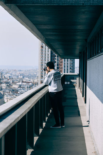 Man standing on railing in city