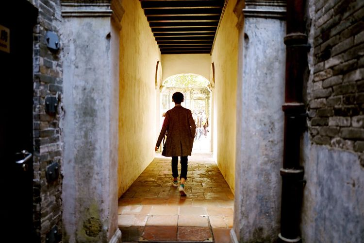 Full Length Rear View Of Man Walking On Narrow Walkway