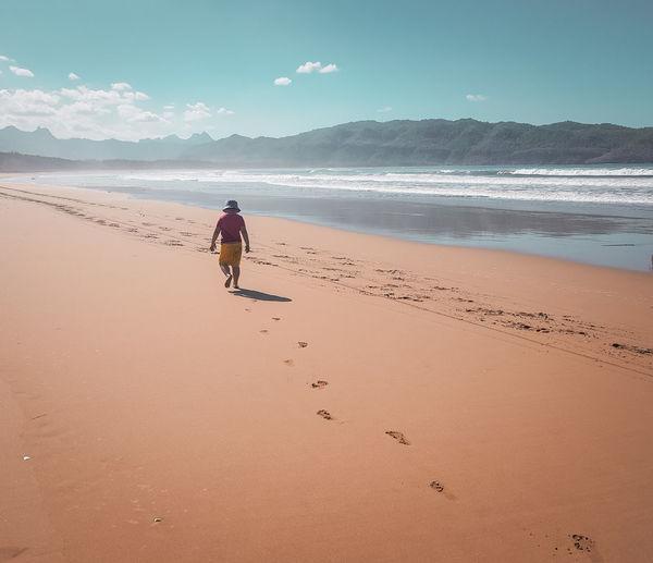 Rear view of boy walking on beach