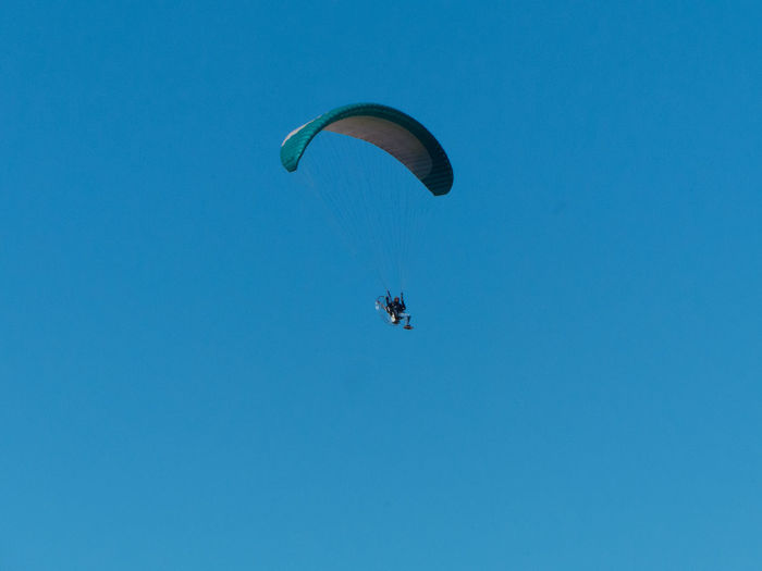 Extreme Sports Sport Adventure Paragliding Parachute Unrecognizable Person Blue Sky Mid-air Leisure Activity Flying Real People Low Angle View Copy Space Clear Sky One Person Lifestyles Day Freedom Transportation Parasailing