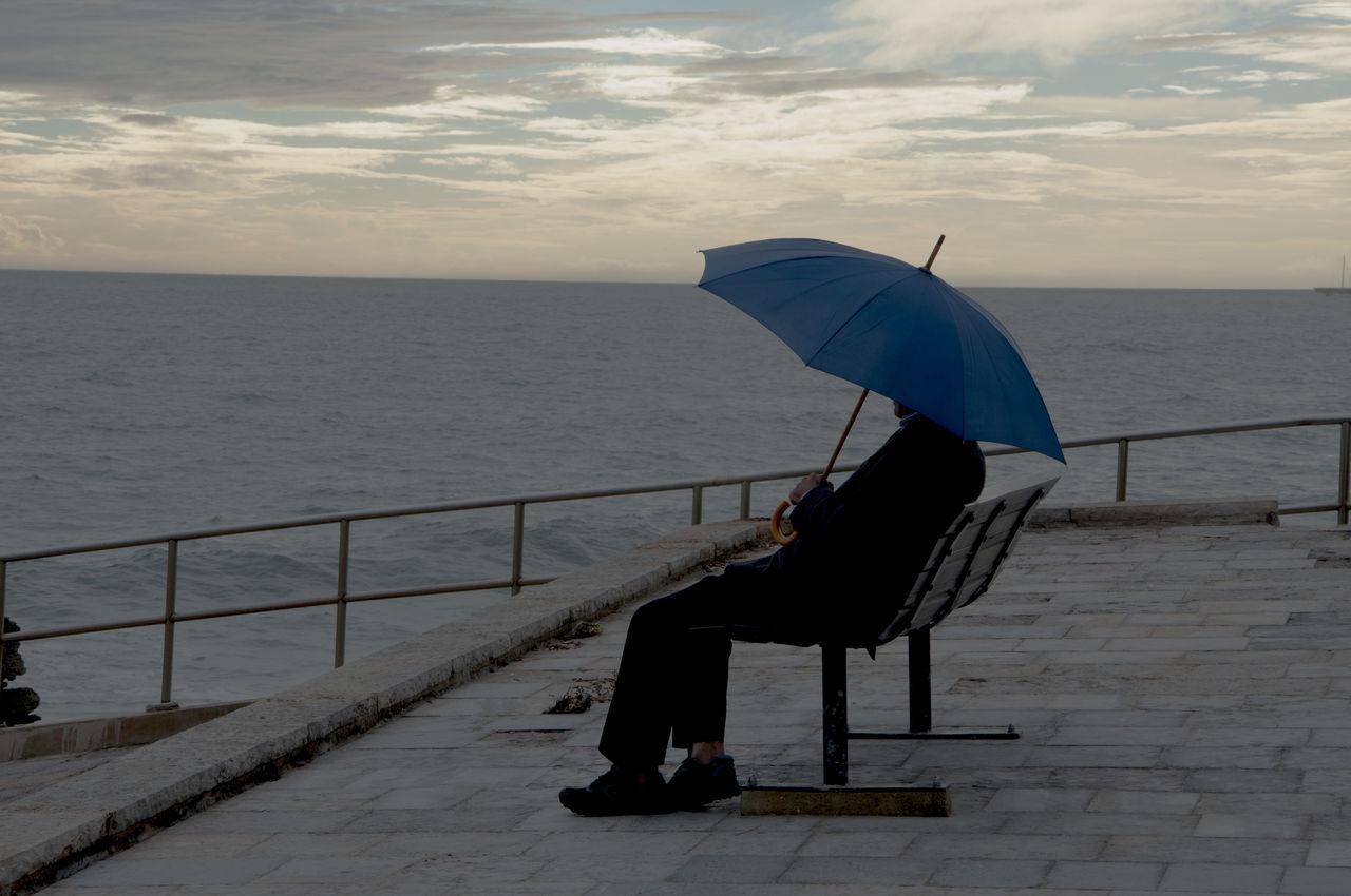 Man Carrying Umbrella Sitting In Promenade Against Sea