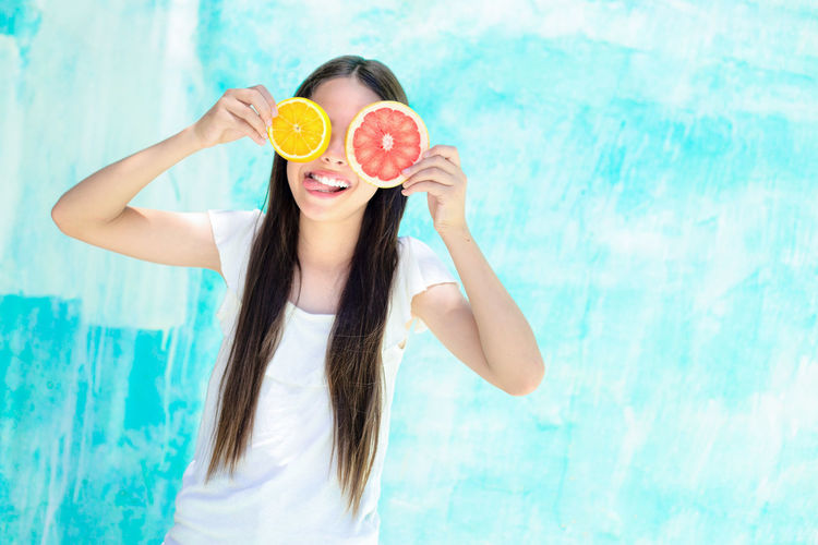 Happy teenage girl holding citrus fruit slices in front of eyes while standing by turquoise wall