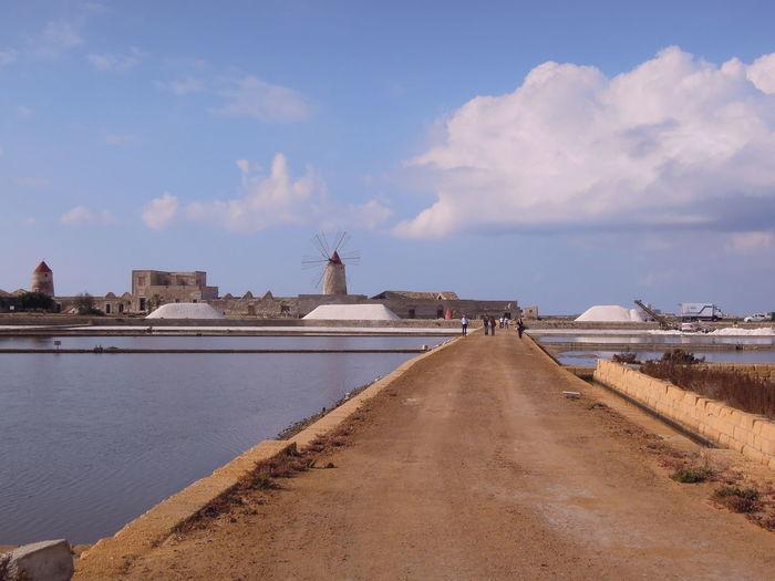 Walkway leading towards salt basin against sky