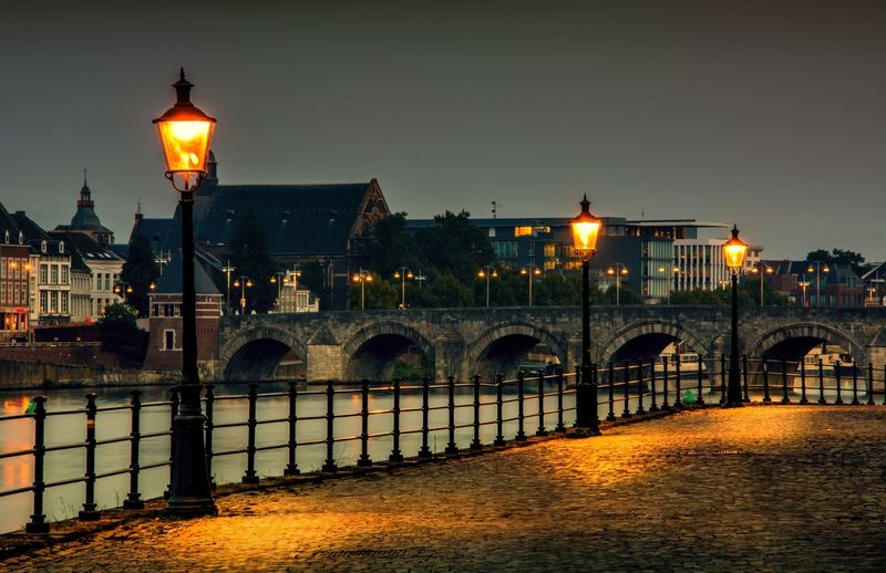 Illuminated street light by river against sky in city at night