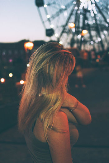 Rear view of woman with illuminated hair in city at night