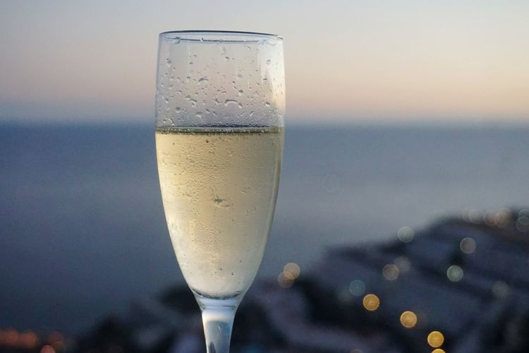 Close-up of champagne glass against sky during sunset