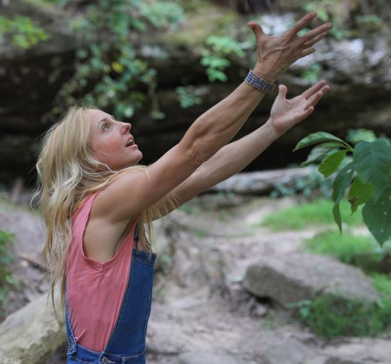 Side view of woman gesturing while standing in forest