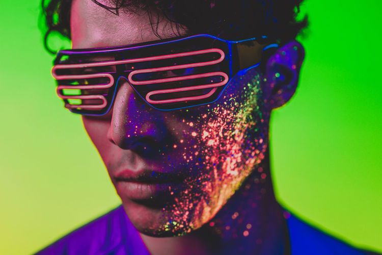 Close-up of man with multi colored face paint wearing eyewear