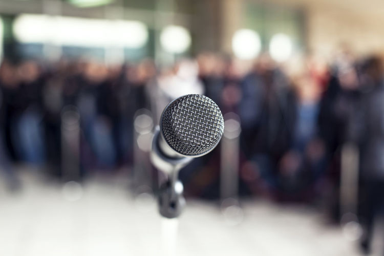 Close-Up Of Microphone With People Standing In Background