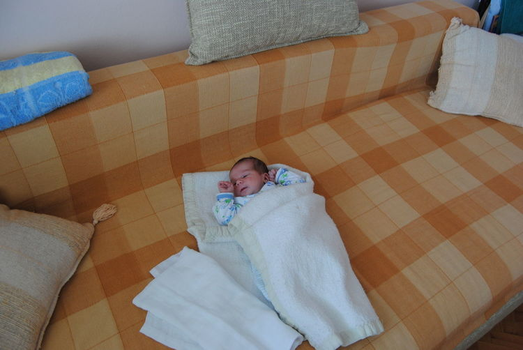 Close-up of cute baby lying on bed at home