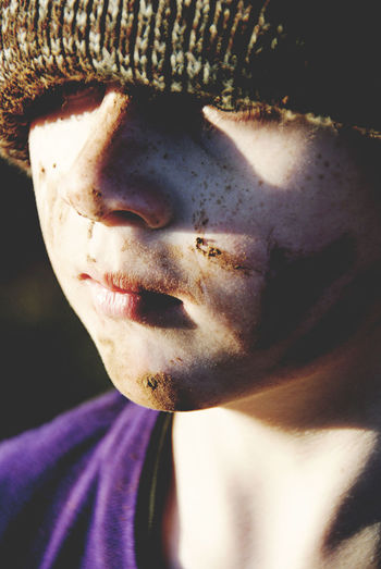 Close-up of boy wearing knit hat with muddy face
