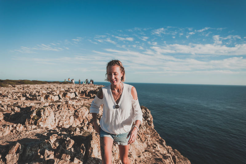 Portrait of smiling woman standing on rock against sea