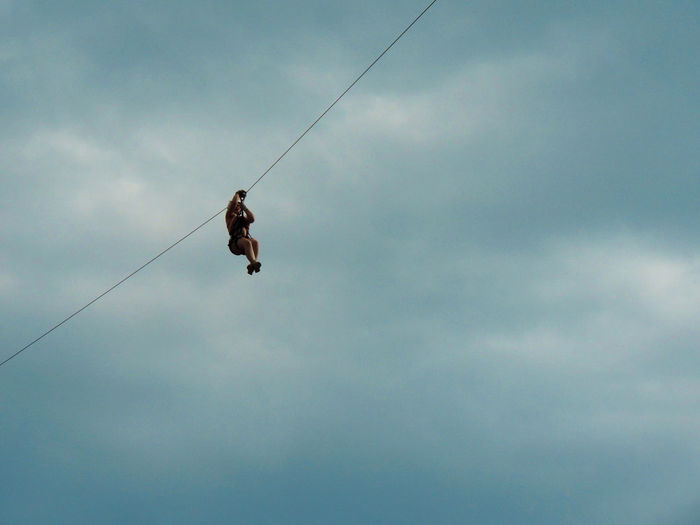 Low Angle View Of Woman Zip Lining Against Cloudy Sky