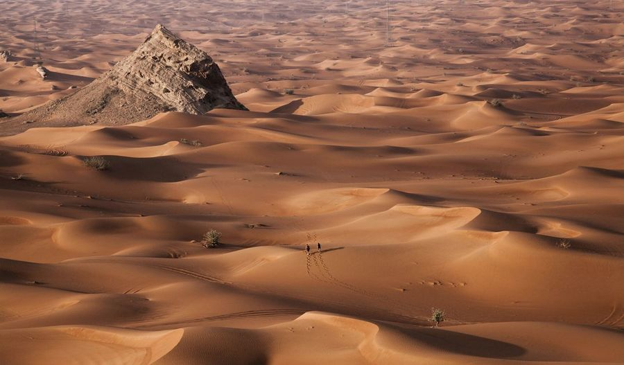 Aerial View Of Two People Travelling Through Desert In Sharjah