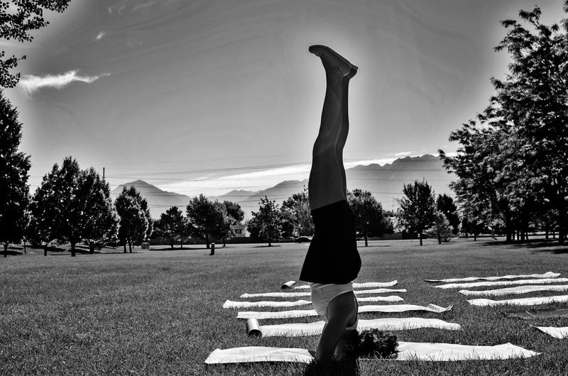Side view of young woman doing handstand on grassy field