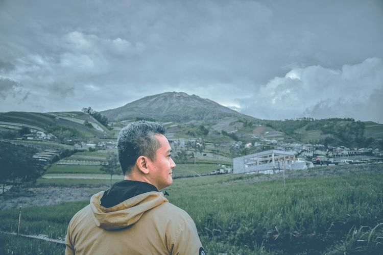 Man standing on field against mountains