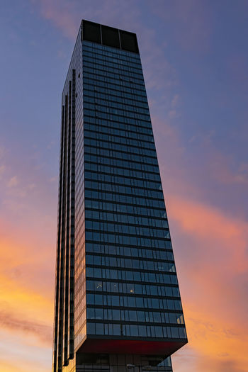 Low angle view of modern building against sky at sunset