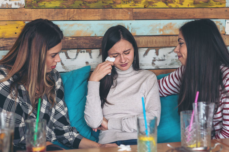 Friends supporting and consoling crying young woman - friendship concept with young millennial girls at restaurant talking about couple problems and divorce – relationship problems of teenagers Woman Crying Friends Young Consoling Talking Sad Girls Group Women Break Friendship Divorce Problems SUPPORT Restaurant Depressed Talk Millennials Upset Unhappy Stress Care Serious Gossip