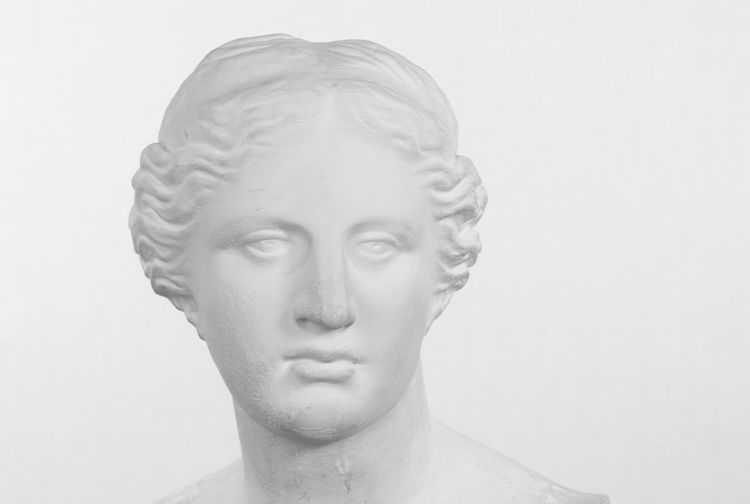 Close-up portrait of statue against white background