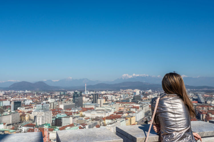 Rear view of woman looking at cityscape against blue sky