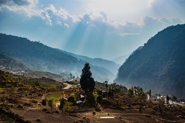 Misty mountain valley with sun rays beams at morning from flat angle