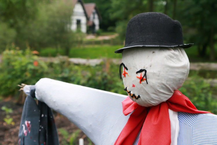 Scarecrow Bird Scarer Bowler Hat Close-up Clothing Day English Garden Focus On Foreground Hat Human Representation Land Lifestyles Men Nature Obscured Face One Person Outdoors Plant Real People Red Scarecrow Uniform Unrecognizable Person Vegetable Garden Vegetables White Color