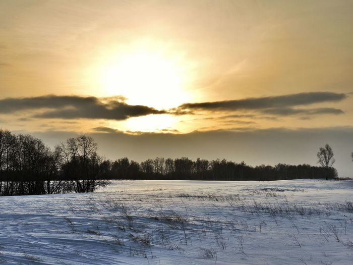 Scenic view of snow covered landscape at sunset
