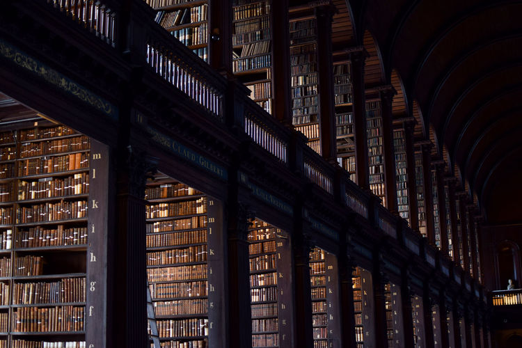 Trinity College Library Corridors  Trinity World Heritage Arch Architectural Column Architecture Book Bookshelf Building Built Structure Ceiling Culture Education History In A Row Indoors  Learning Library Literature Low Angle View No People Publication Repetition Shelf The Past