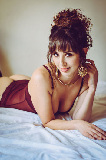 Portrait Of Smiling Young Seductive Woman Lying On Bed At Home