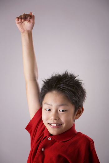 Portrait of smiling boy with hand raised white background