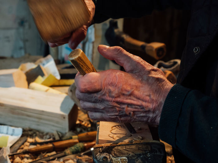 Midsection of man carving wood in workshop