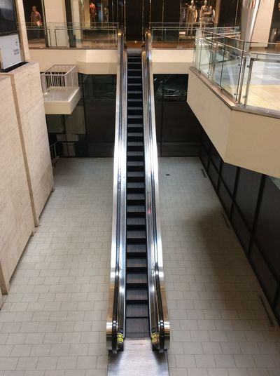 USA Texas Houston In The Shopping Mall single lane escalator mall shops Mall Floor Tiles shiney metal surfaces Manakins railings Reflections