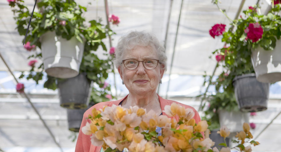 Portrait of senior woman with flowers in flower market