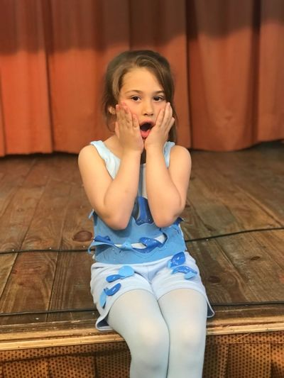 Portrait of shocked girl sitting on stage