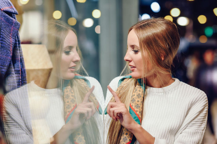 Young woman looking through store window in city at night