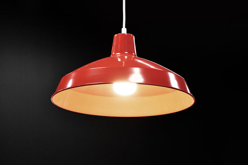 Close-up of illuminated pendant light over black background
