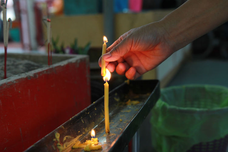 Close-up of hand holding lit candles in temple