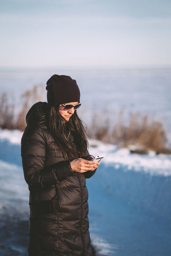 Woman wearing winter jacket using mobile phone on snow covered field