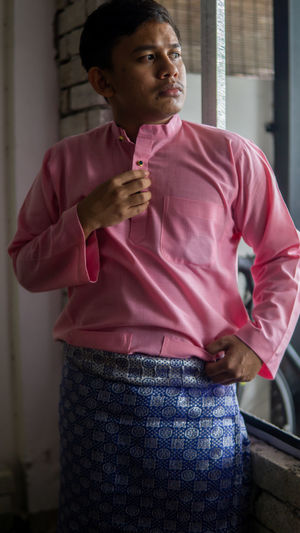 Man looking away while standing on pink indoors