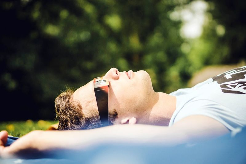 Close-up of man wearing 3-d glasses while lying on field