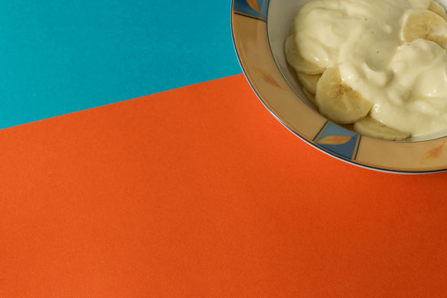 Bowl of sliced banana and yoghurt in a bowl on bright orange and blue background - minimal, copy space EyeEmNewHere Yogurt Yoghurt And Fruit Yoghurt Sweet Snack Sliced Banana Simple Food Simple Beauty Minimalism Minimal Geometric Fruit Bright Colours Bowl Blue Banana And Yoghurt Background After School Snack Healthy Snack From Above  Everyday Food Everyday Life Copy Space Banana