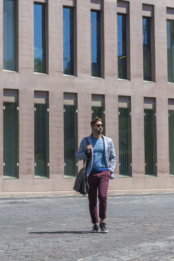 Full length of man walking by building in city