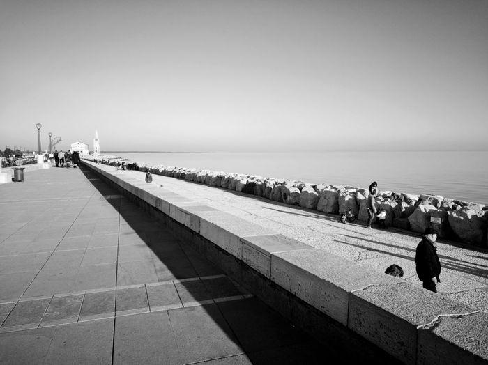 People on promenade against clear sky