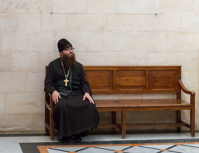Jerusalem, Israel, November 17, 2018 : Orthodox priest sitting on a bench in Alexander Nevsky church in Jerusalem, Israel Jerusalem Israel Jesus Christ Religion Orthodox History Heritage Icon Christianity Alexander Nevsky Church Interrior Russian Old City Palestine Holy Wall - Building Feature Stone Material Cross Travel Destinations Pilgrimage Altar Tourism Prayer Landmark Bible Culture