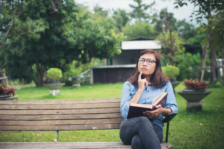 Thoughtful young woman looking away while holding book on park bench